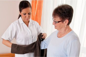 caregiver assists the elderly woman to dress up
