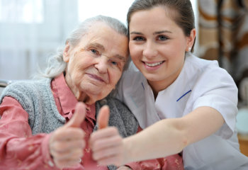 elderly woman and her caregiver thumb's up