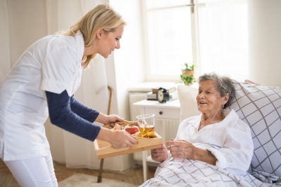 caregiver bringing breakfast to a sick senior women lying in bed at home